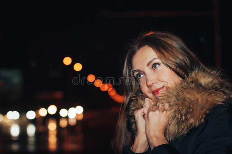 Портрет славной девушки в теплом пальто в темном городе стоковая фотография rf
