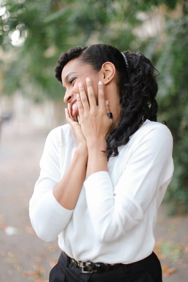 Портрет славной молодой афро американской женской персоны с ponytail и кольцом усмехаясь с белыми зубами стоковые фото