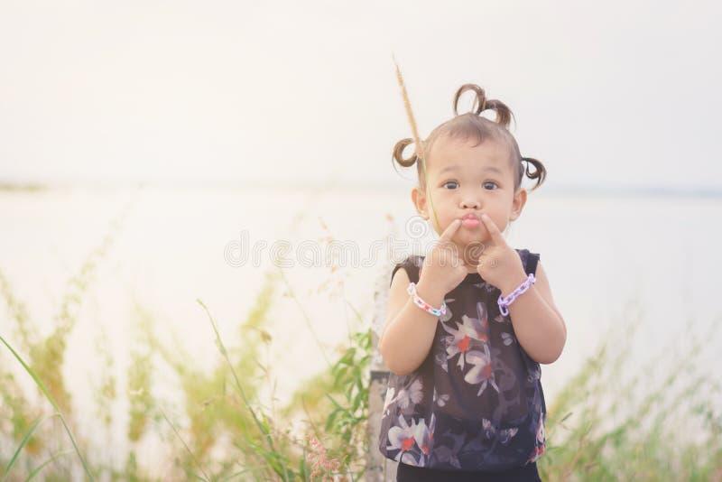 Портрет сладостного и милого азиатского ребенк с волос оплетки дверью вне на стоковое изображение