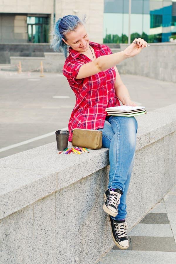 Портрет случайное милого и маленькая девочка с голубыми волосами в джинсах городским летом рисуя или писать стоковое изображение