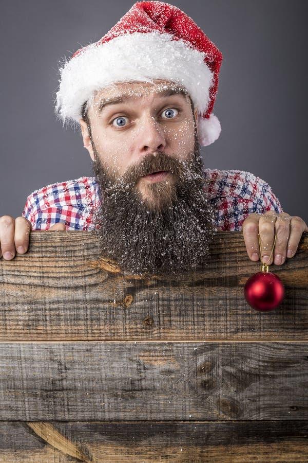 Портрет смешного бородатого человека при крышка santa держа красное rou стоковые фотографии rf