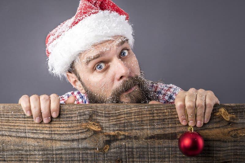 Портрет смешного бородатого человека при крышка santa держа красное rou стоковая фотография rf