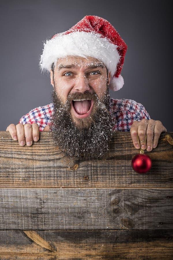 Портрет смешного бородатого человека при крышка santa держа красный декабрь стоковая фотография rf