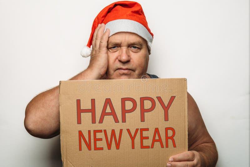 Портрет смешного старшего человека в красной шляпе рождества Санта Клауса держит картон с Новым Годом надписи счастливым в руках стоковая фотография