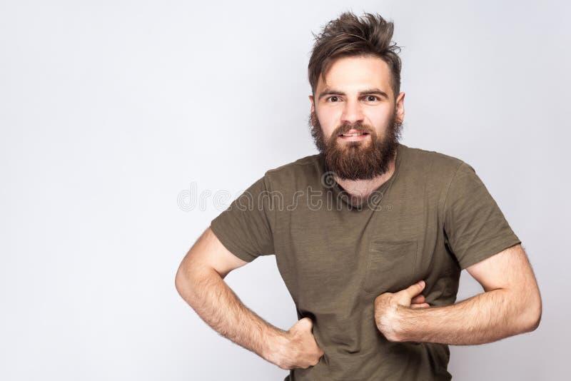 Портрет смешного шального бородатого человека с темной ой-зелен футболкой против света - серой предпосылки стоковое изображение rf