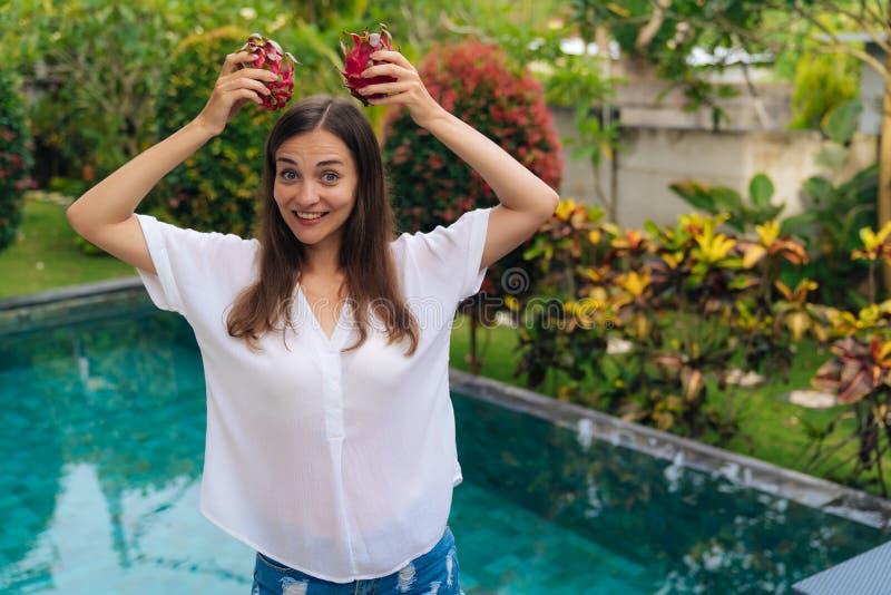 Портрет смешной девушки имеет радостное выражение и держит 2 плода дракона наверху стоковая фотография