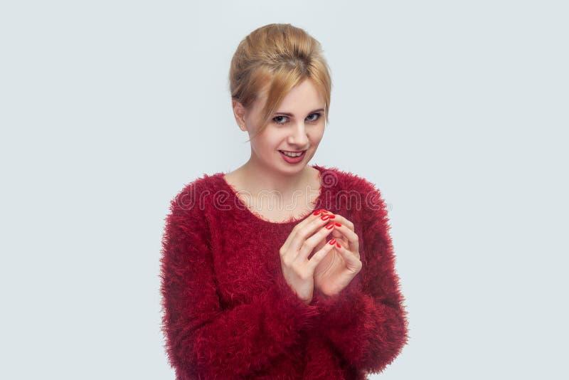 Портрет смешной красивой молодой белокурой женщины в красном положении блузки в хитром обжуливая жесте рук и смотреть камеру с стоковая фотография