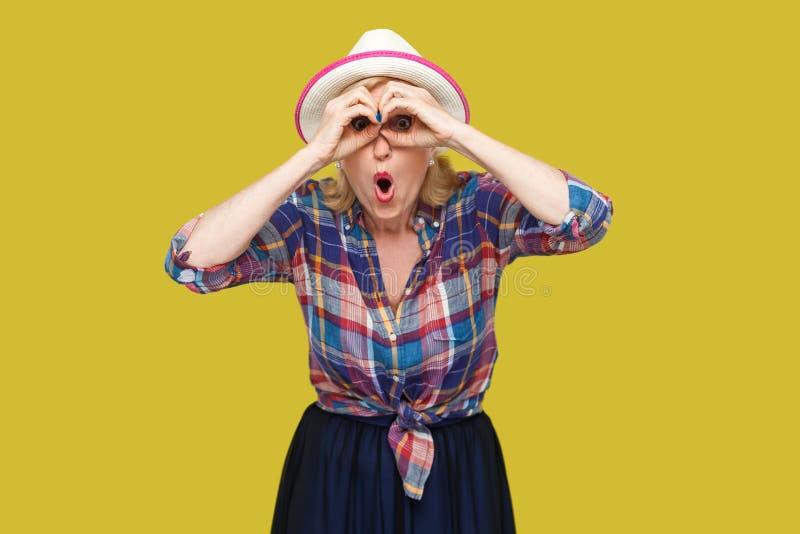 Портрет смешной удивленной современной стильной зрелой женщины в непринужденном стиле с положением шляпы с биноклями показывает ж стоковые фото