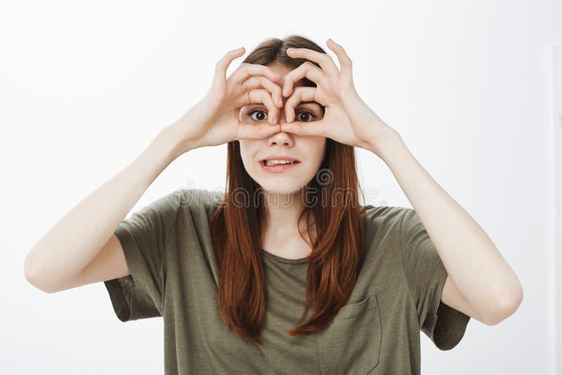 Портрет смешной эмотивной очаровательной женщины в вскользь одеждах держа о'кей подписывает сверх глаза если держащ бинокулярный, стоковая фотография rf