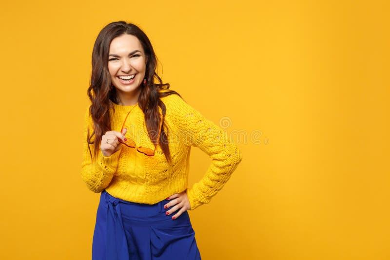 Портрет смеясь молодой женщины в свитере, голубых брюках держа стекла стоя смотрящ камеру изолированную на желтом цвете стоковые изображения