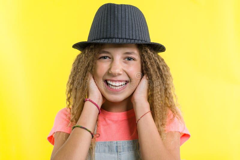 Портрет смеяться над предназначенной для подростков девушкой в шляпе, смотря камеру над желтой предпосылкой стоковые изображения