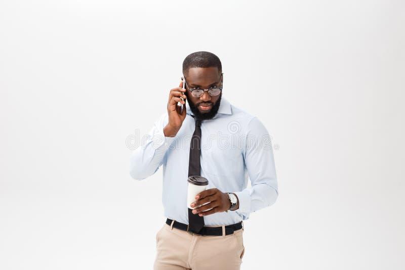 Портрет смущенного молодого африканского человека одетого в белой рубашке говоря на мобильном телефоне и показывать жестами изоли стоковые изображения