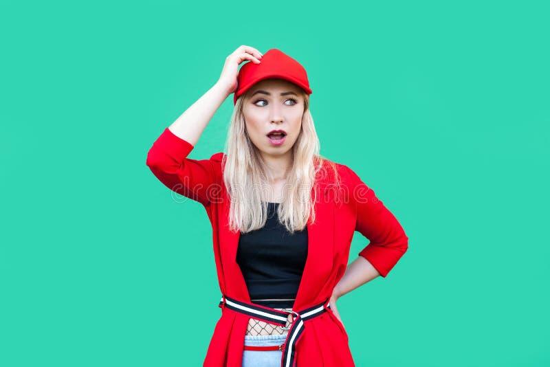 Портрет смущенной белокурой молодой женщины хипстера в красной блузке, крышке, стоящ с рукой на талии и на голове смотря прочь со стоковое фото rf