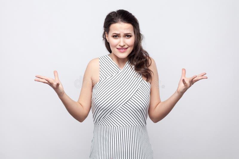 Портрет смущенной красивой молодой женщины брюнета с макияжем и striped положением платья и смотреть камеру с сердитой стороной стоковое изображение