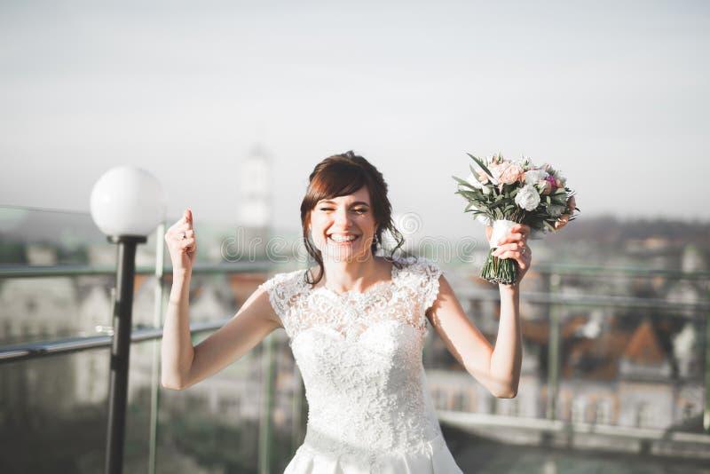 Портрет сногсшибательной невесты с длинными волосами представляя с большим букетом стоковое изображение