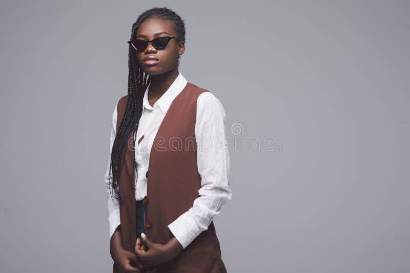 Портрет солнечных очков африканской женщины нося и модных одежд стоя против серой предпосылки стоковое фото