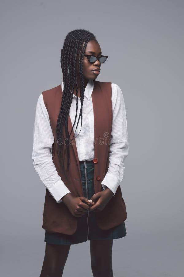 Портрет солнечных очков африканской женщины нося и модных одежд стоя против серой предпосылки стоковые изображения rf