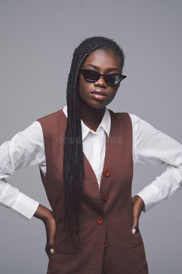 Портрет солнечных очков африканской женщины нося и модных одежд стоя против серой предпосылки стоковые фотографии rf
