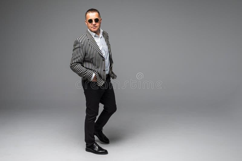 Портрет солнечных очков старшего более старого бизнесмена стоя нося темных изолированных на белой предпосылке стоковые фотографии rf