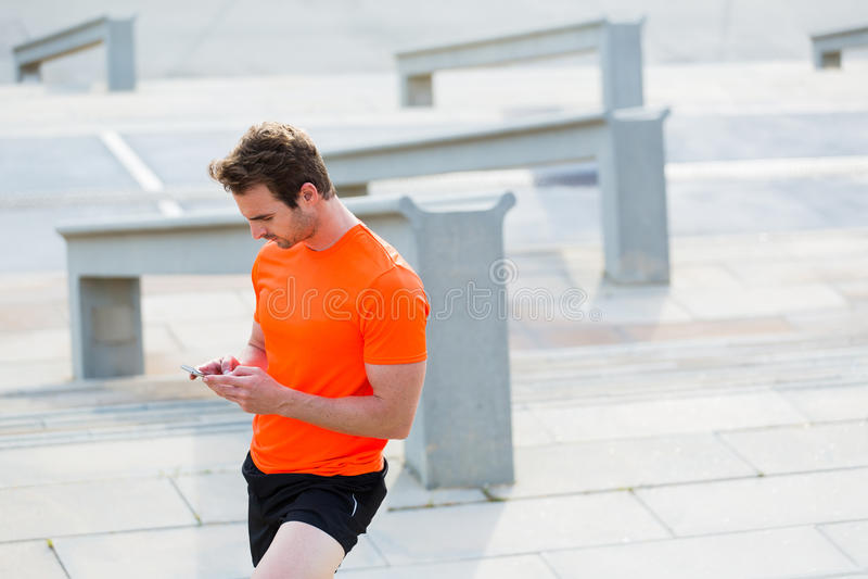 Портрет сообщения мужского jogger печатая на его телефоне клетки пока принимающ пролом между физическими упражнениями стоковые изображения rf