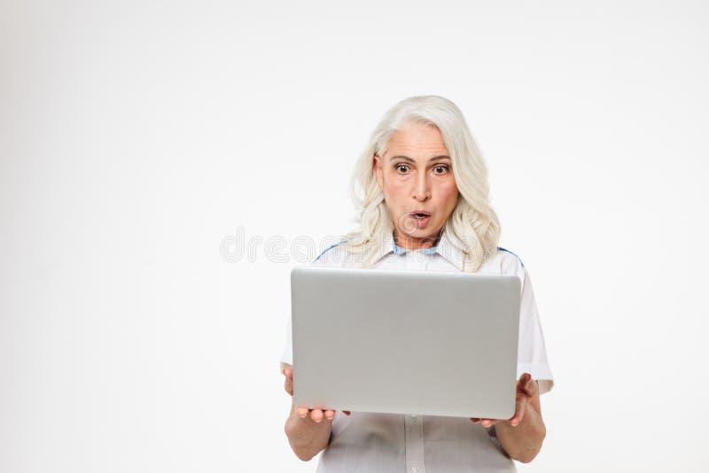 Портрет сотрясенной зрелой женщины смотря компьтер-книжку стоковое фото