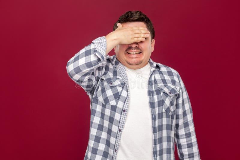 Портрет сотрясенной красивой середины постарел бизнесмен в случайном checkered положении рубашки, закрыл его глаза с рукой и не д стоковые изображения rf