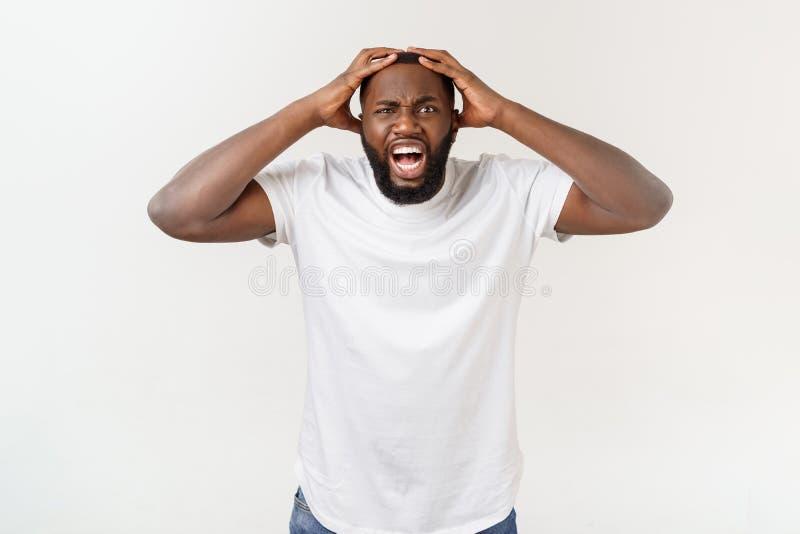 Портрет сотрясенной футболки молодого Афро-американского человека нося белой пустой смотря камеру в сюрпризе, оглушил стоковое фото rf