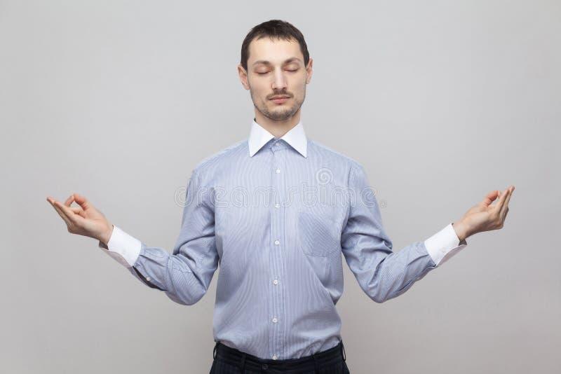 Портрет спокойного красивого бизнесмена щетинки в классическом свете - голубом положении рубашки в представлении йоги с закрытыми стоковые фотографии rf