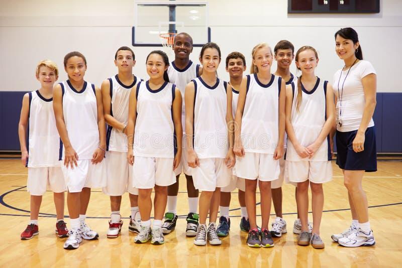 Портрет спортивной команды средней школы в спортзале с тренером стоковое изображение rf