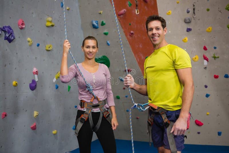 Портрет спортсменов держа веревочку пока готовящ взбираясь стену стоковая фотография