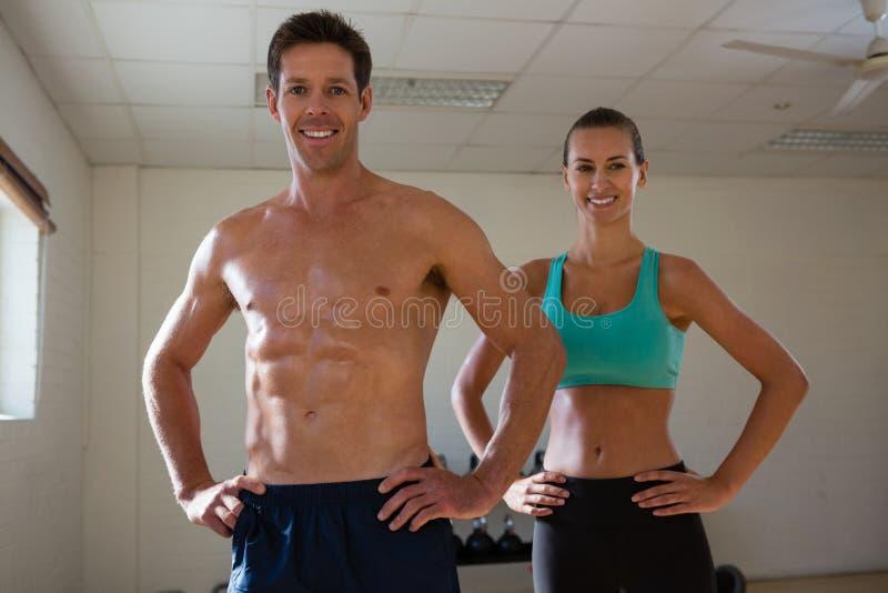 Портрет спортсменов пригонки с руками на бедре на фитнес-клубе стоковые изображения