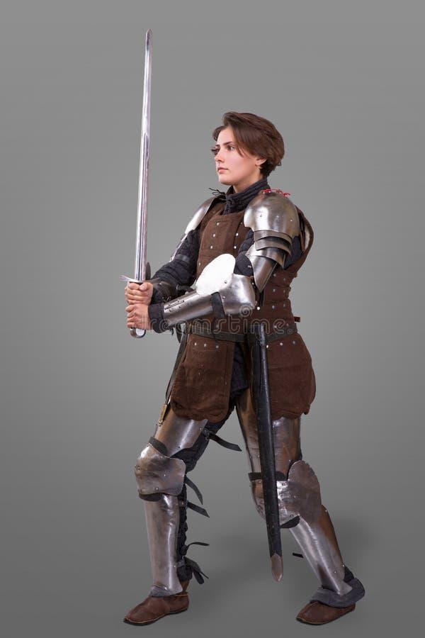 Портрет средневекового женского рыцаря в панцыре над серой предпосылкой стоковая фотография rf
