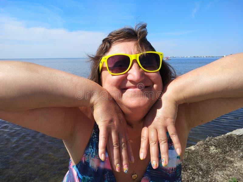 Портрет средн-достигшего возраста положения женщины против моря и hernails показывать покрытых с шеллаком стоковое изображение rf