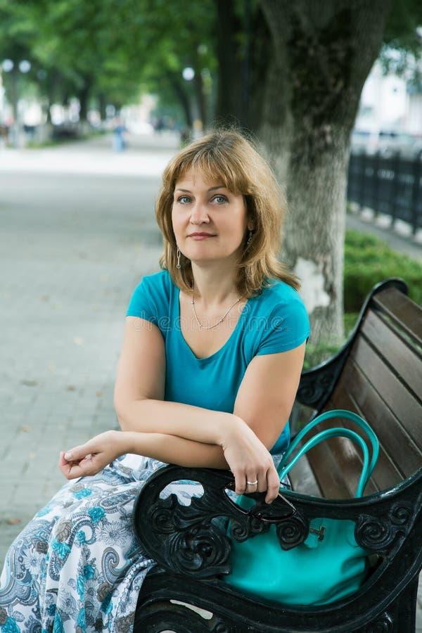 Портрет средн-постаретой женщины сидя на стенде стоковые фото