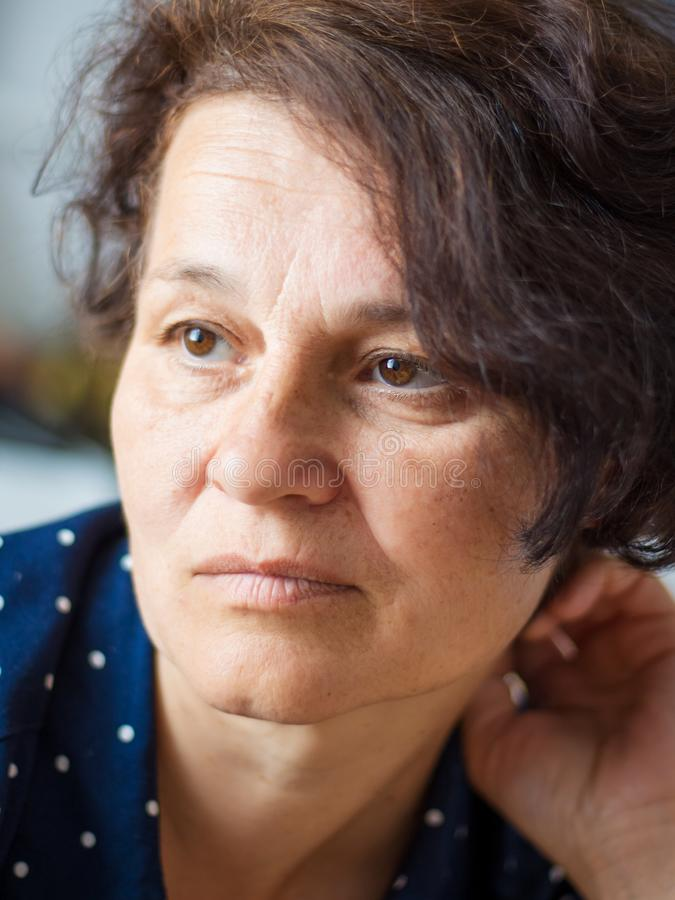 Портрет средн-постаретой женщины с унылым выражением для сторон стоковое фото