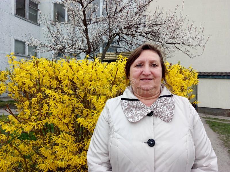 Портрет средн-постаретой женщины на предпосылке желтого куста стоковые фото