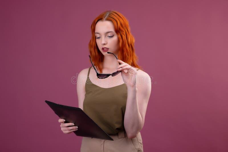 Портрет старательного студента девушки с папками и солнечными очками университет или коллеж на розовой предпосылке стоковое фото