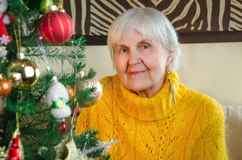 Портрет старой бабушки дома в Новом Годе кавказская положительная, дружелюбная бабушка в праздничном, белом связанном свитере стоковое изображение