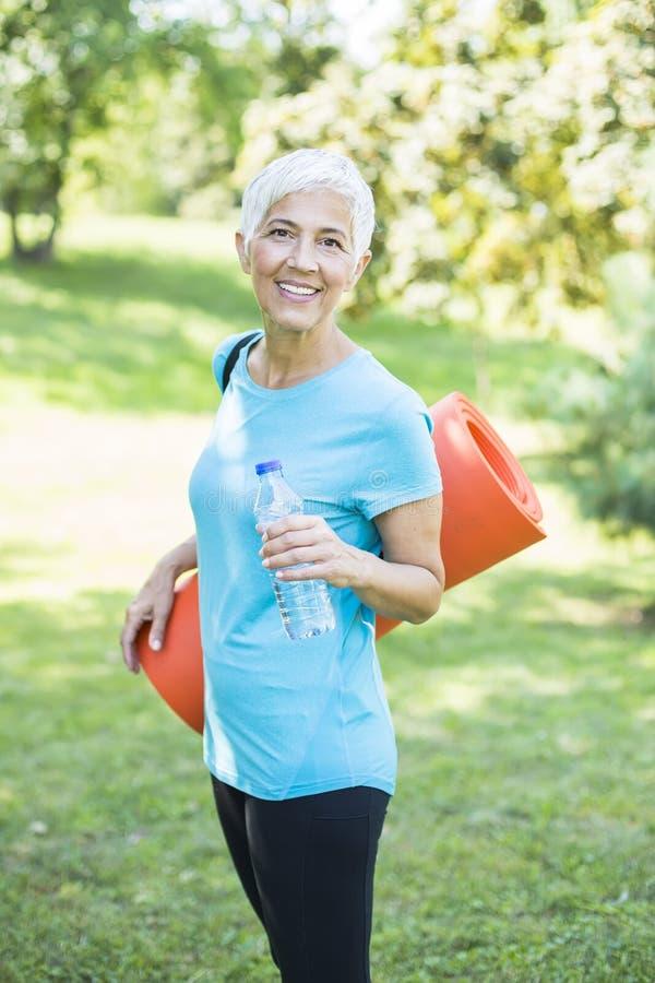 Портрет старшей женщины держит циновку фитнеса на ей назад в парке и подготовке для тренировки стоковые изображения rf