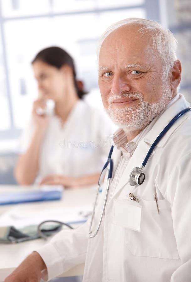 Портрет старший усмехаться доктора стоковые фото