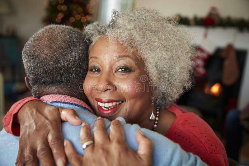 Портрет старших пар обнимая по мере того как они празднуют рождество дома совместно стоковое изображение