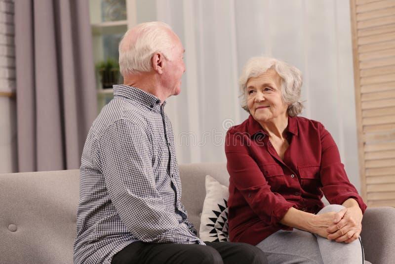 Портрет старших супругов сидя на софе стоковое изображение rf