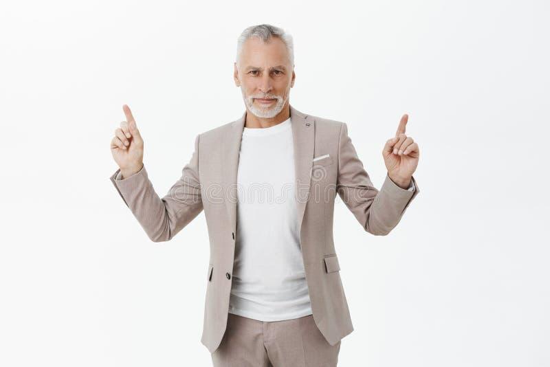 Портрет стильного красивого счастливого старого мужского предпринимателя в сером костюме с белой бородой и волос указывая вверх и стоковое изображение rf