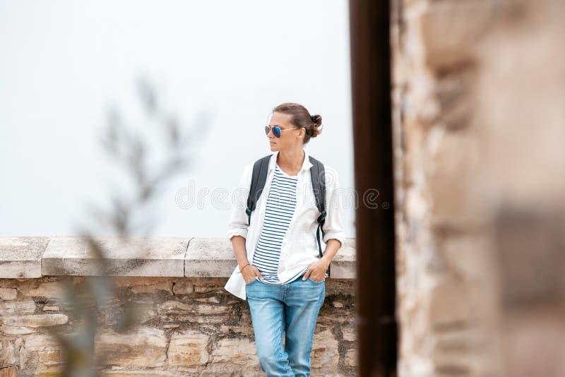 Портрет стильной молодой женщины в джинсах и белой рубашке дальше стоковое изображение
