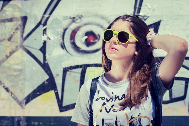 Портрет стильного девочка-подростка в солнечных очках представляя около gra стоковое изображение rf