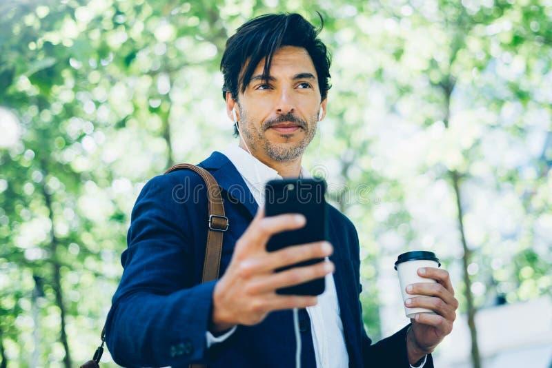 Портрет стильного молодого бизнесмена используя smartphone для listining музыки пока идущ в парк города и держащ взятие стоковое фото rf