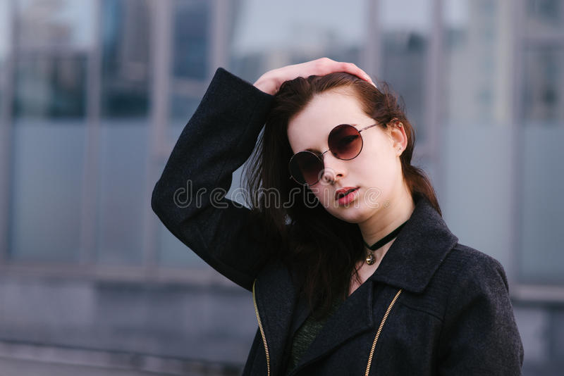 Портрет стильно одел брюнет женщин красивое в стеклах, которое представляет против предпосылки темной предпосылки города стоковые изображения