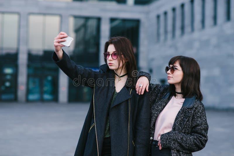 Портрет 2 стильных женщин нося битника которые сфотографированы на smortfon стоковые фото