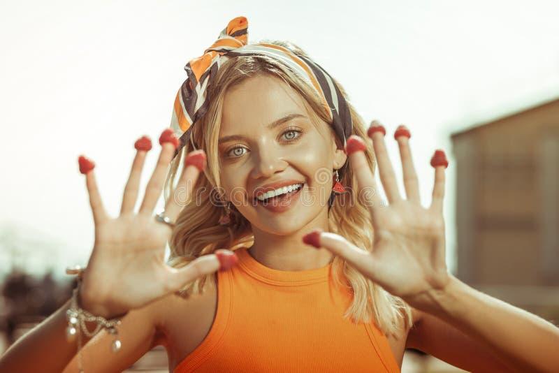 Портрет стороны дамы показывая пальцы с клубниками на их стоковые фото