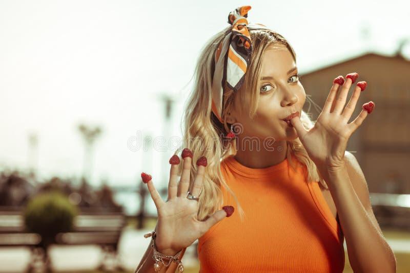 Портрет стороны молодой женский представлять с клубниками на пальцах стоковые изображения
